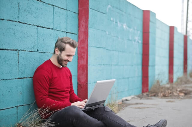 man leaning against wall with laptop and laughing