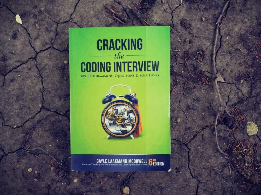 Cracking the Coding Interview book laying on dry cracked earth
