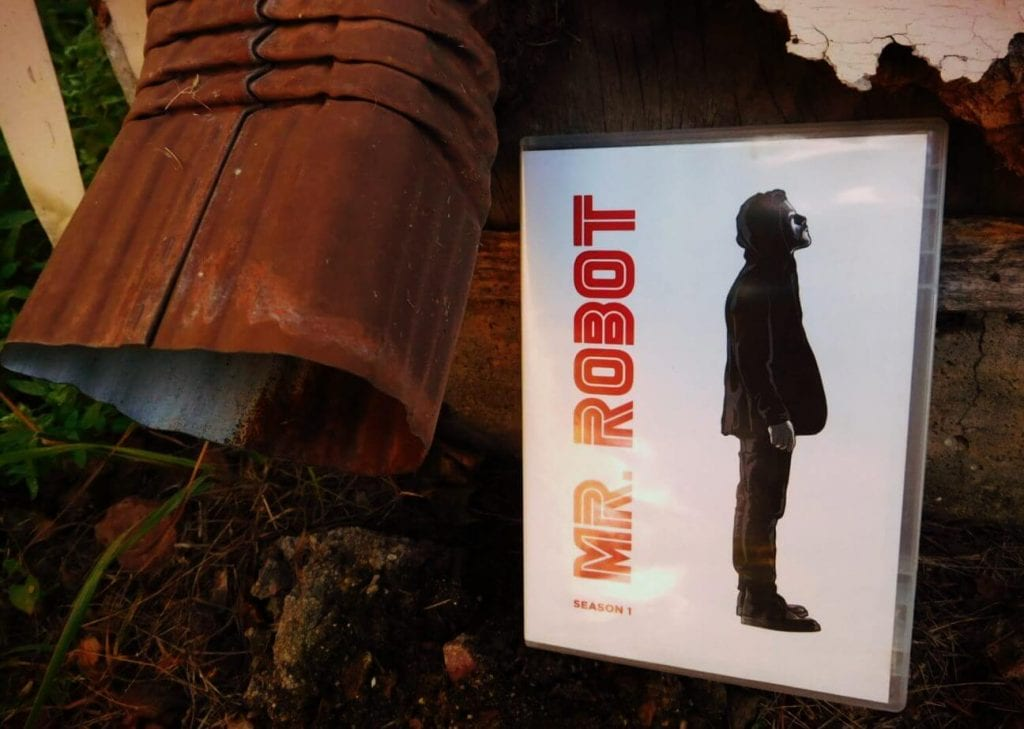 closeup of rain gutter and Mr. Robot DVD case with red text and side view of standing man