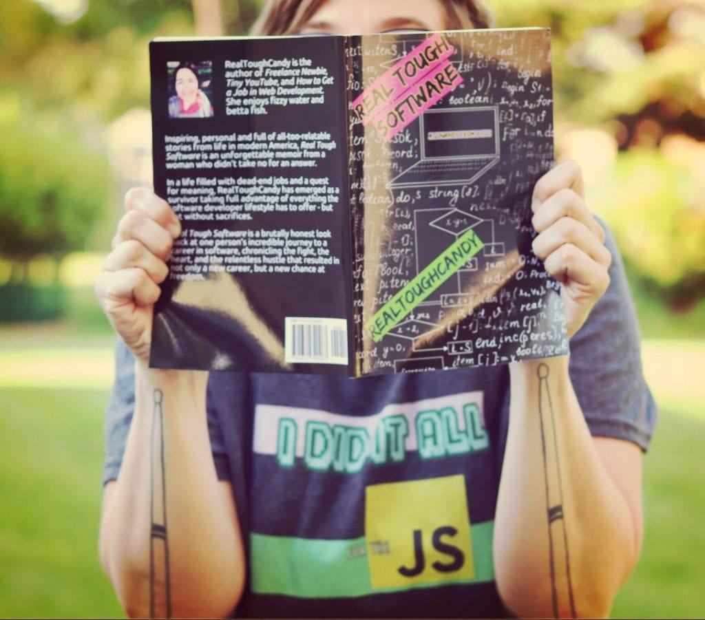 girl with I Did it All for the JS JavaScript shirt holding up Real Tough Software book